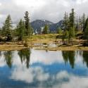 Reflets de nuages dans le lac de Graveirette, (2239 m), le mont Archas, (2526 m), un peu caché par les nuages, puis la cime de la vallette des Adus, (2449 m), dans le vallon de Mollières. Mélézin clairsemé sur les bords du lac.